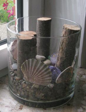 Glasschale mit Holz und Muscheln