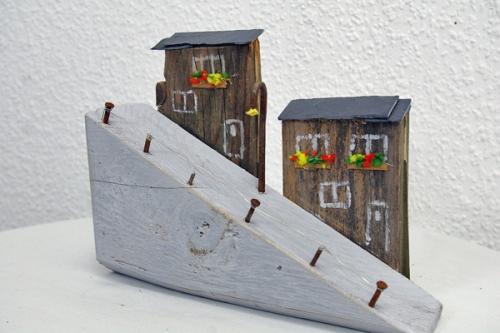 Naturstrandhaeuser als Mini-Landschaften gebaut aus Treibholz und Farbe