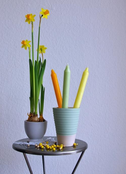 Narzissen, Osterglocken und Kerzen zur Dekoration