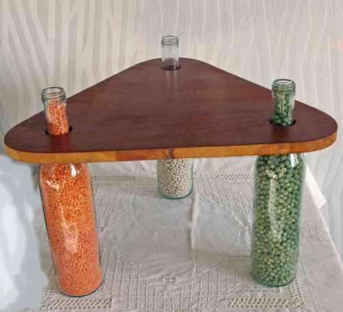 kleiner Holztisch mit Flaschen