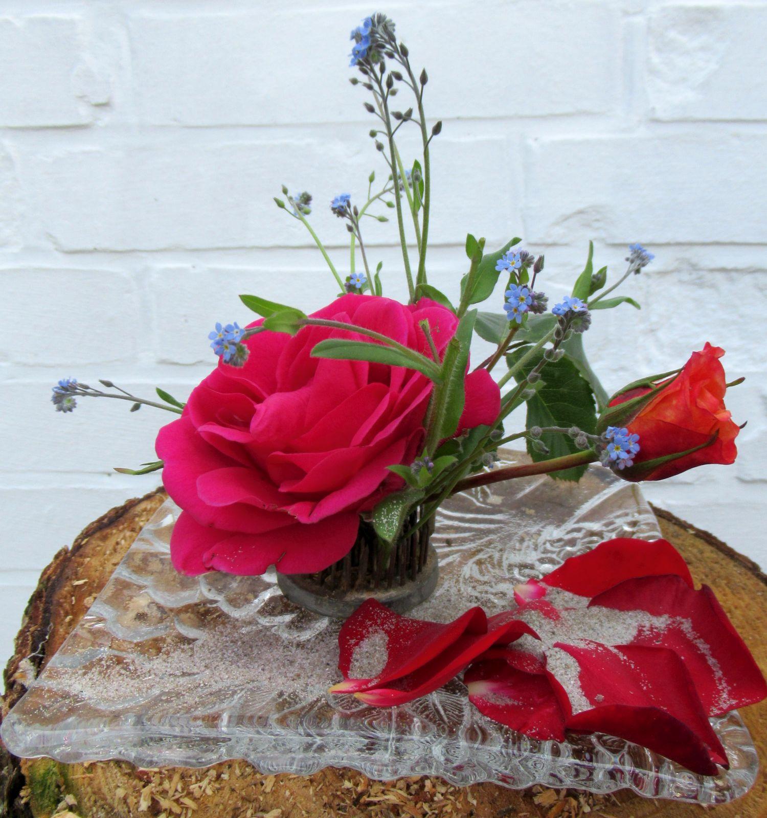 Dekoration mit Rosen und Vergissmeinnicht auf einem Glasteller