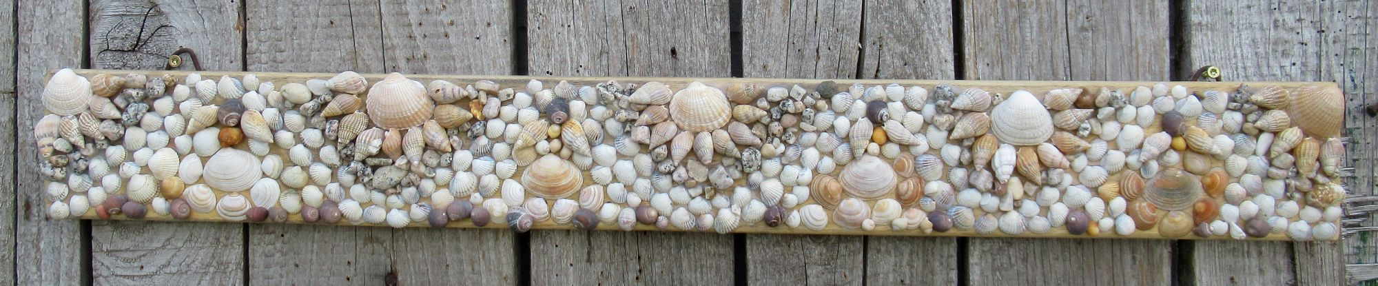 Ein Muschelbild auf Holz für die Sommerdekoration im Garten