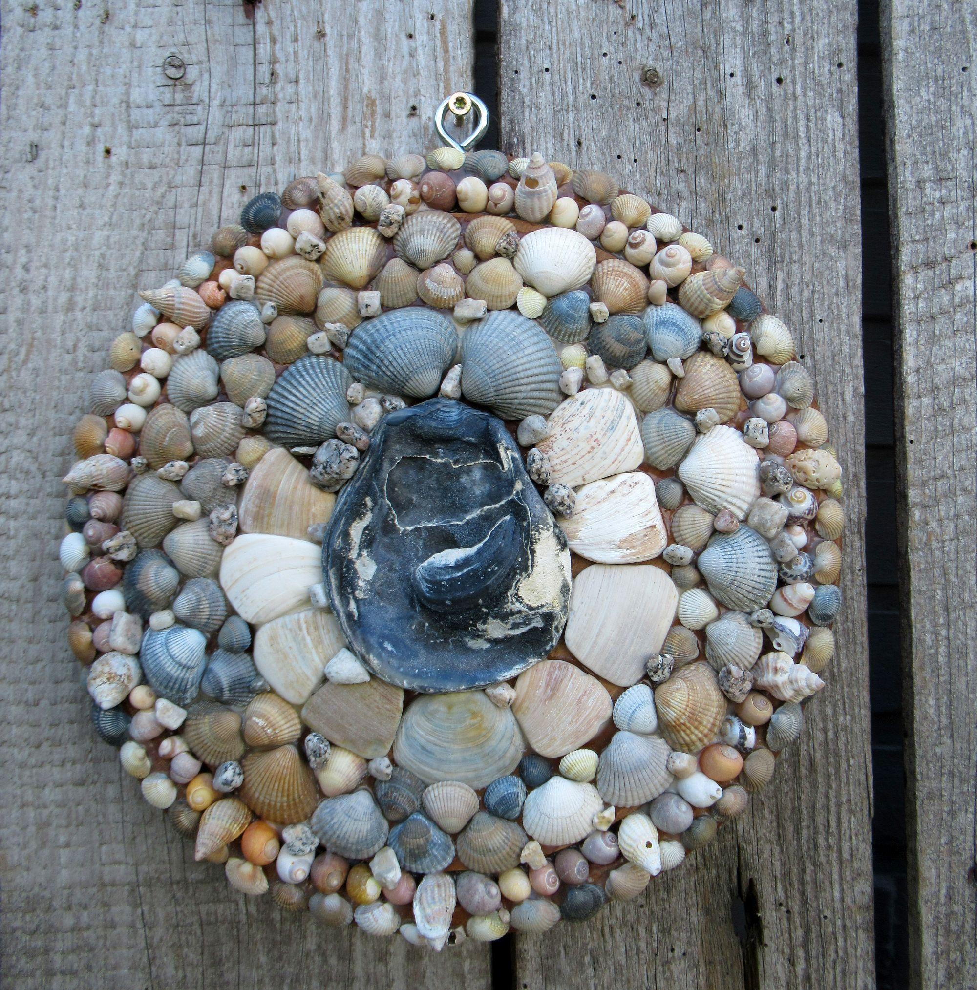 Mandala aus Muscheln auf ein Holzbrett geklebt