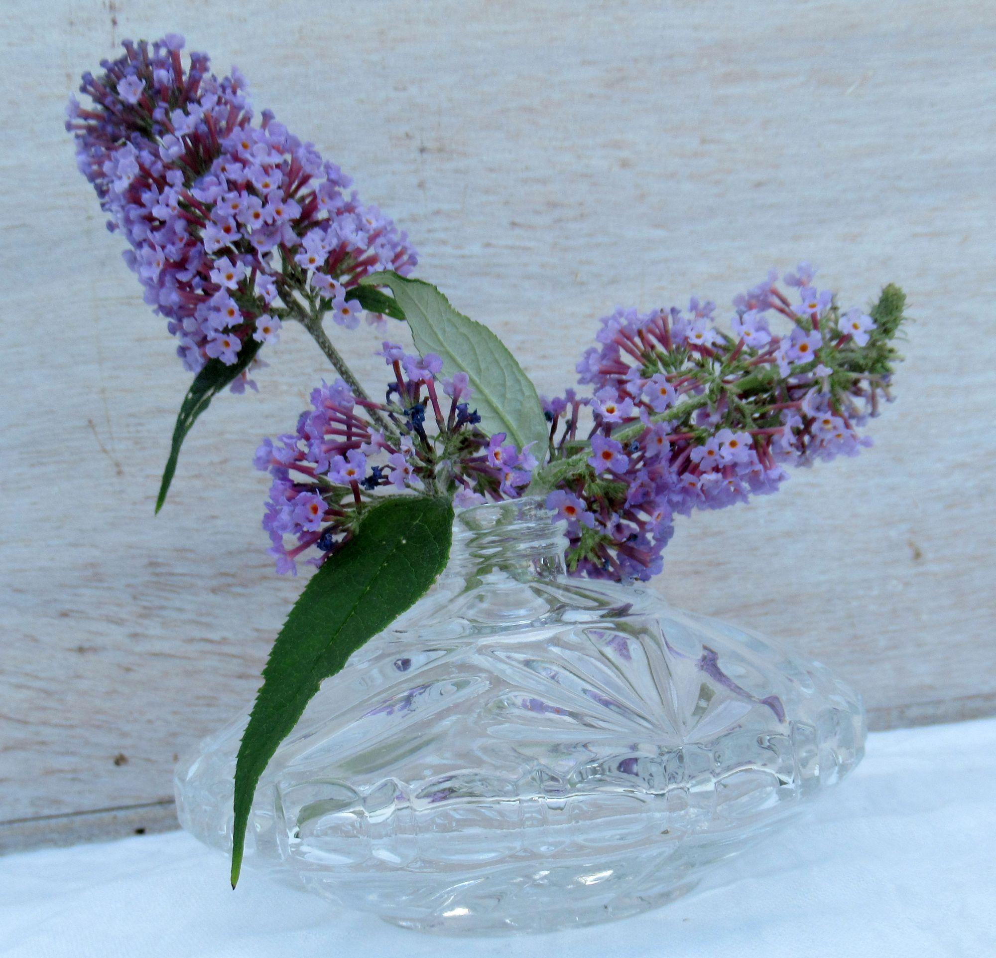 wenige Fliederblüten in der schön strukturierten Glasvase als Sommerdeko