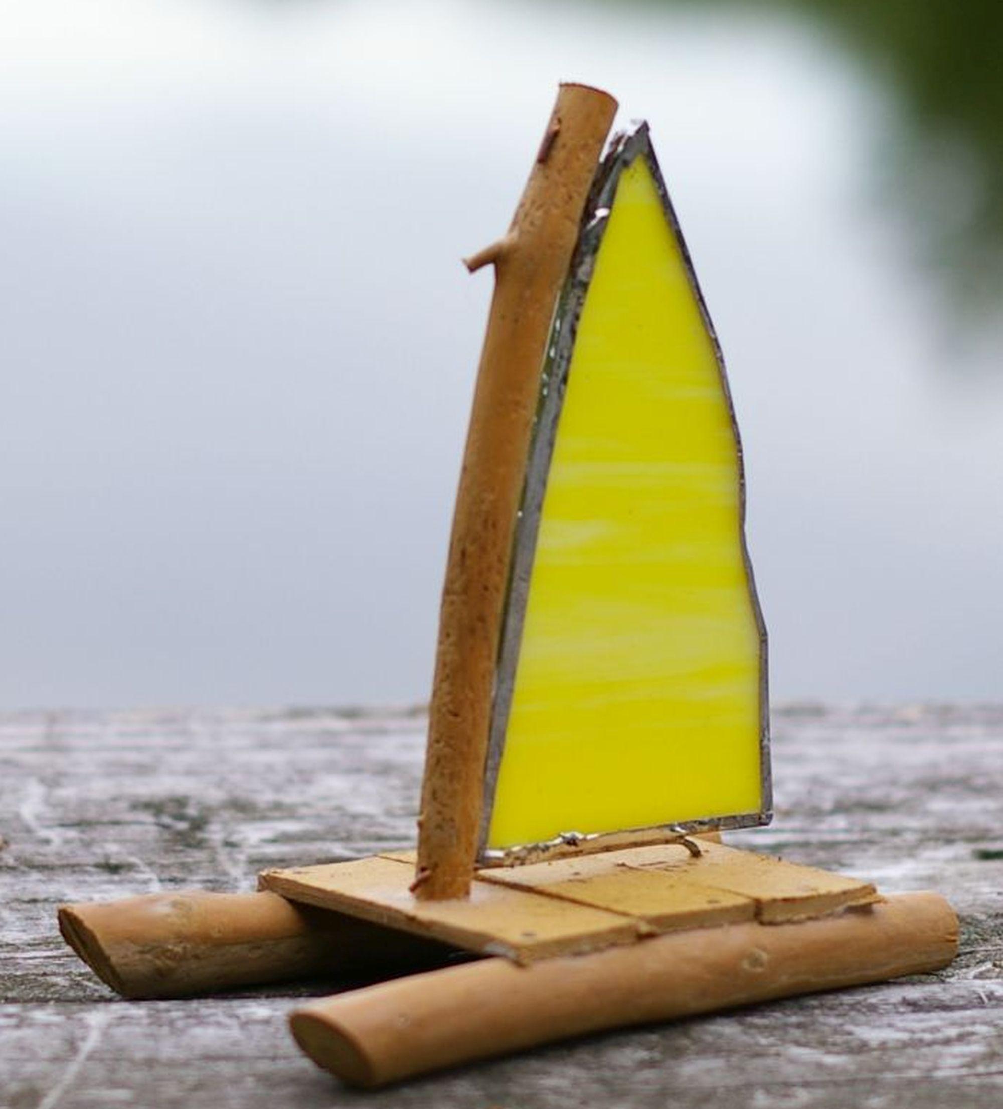 ein Mini-Katamaran aus Treibholz mit Glassegeln