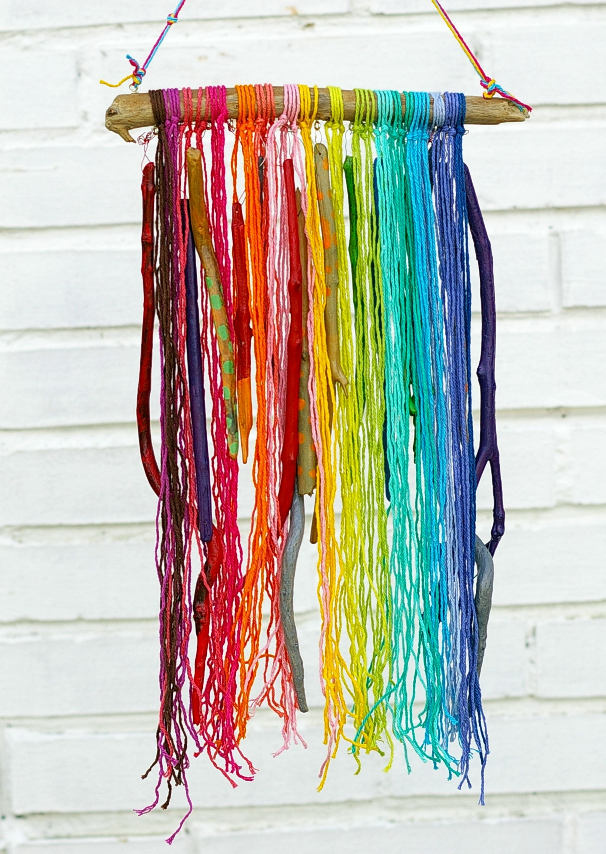 Windspiel mit bunter Wolle und Holz in Regenbogenfarben