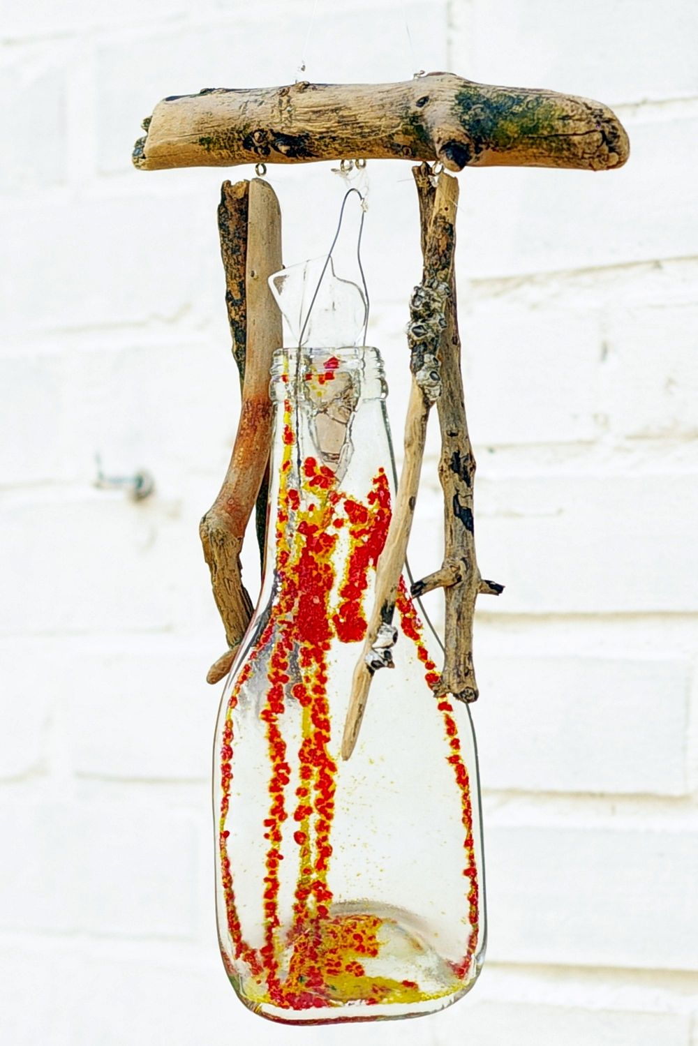 Mobile mit geschmolzener Glasflasche und Treibholz als Gartendeko